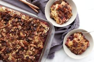 top down view of oatmeal, pecans, and raisins casserole in two bowls and a pan