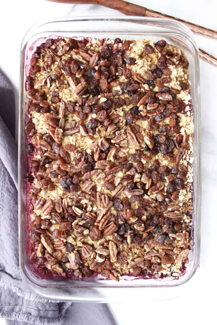 flat lay of casserole with oatmeal, raisins, and pecans in rectangular pyrex pan