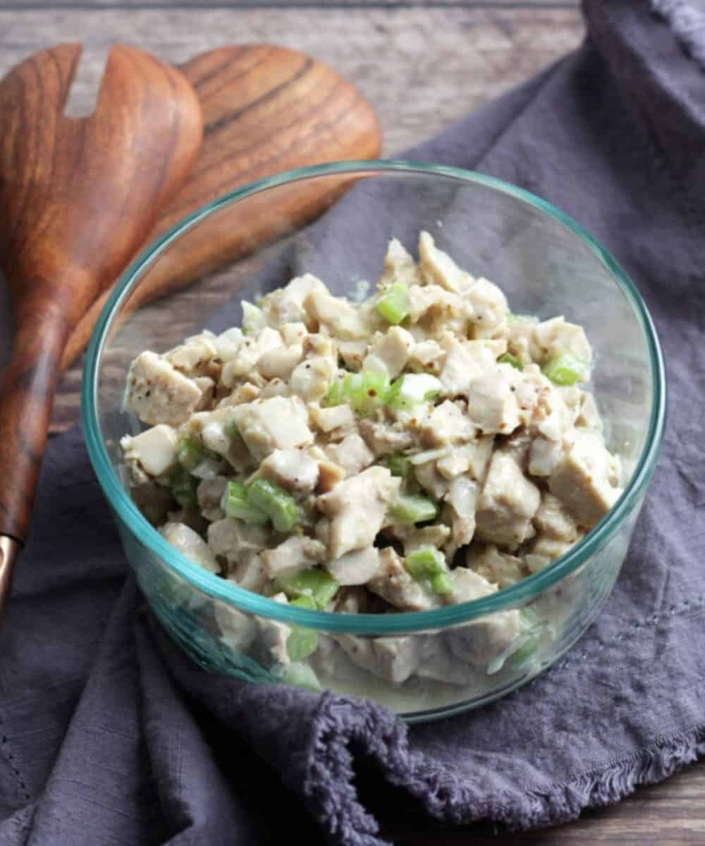 chicken salad with celery in glass bowl on lavender napkin with wooden spoons