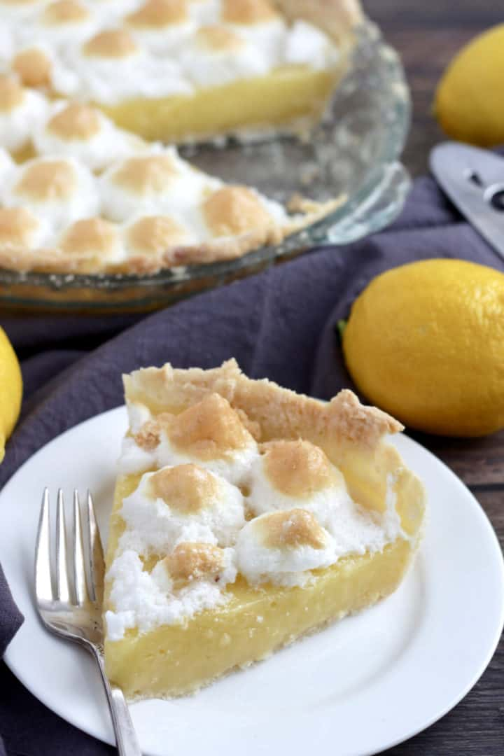 slice of lemon meringue pie on white plate with remaining pie in background