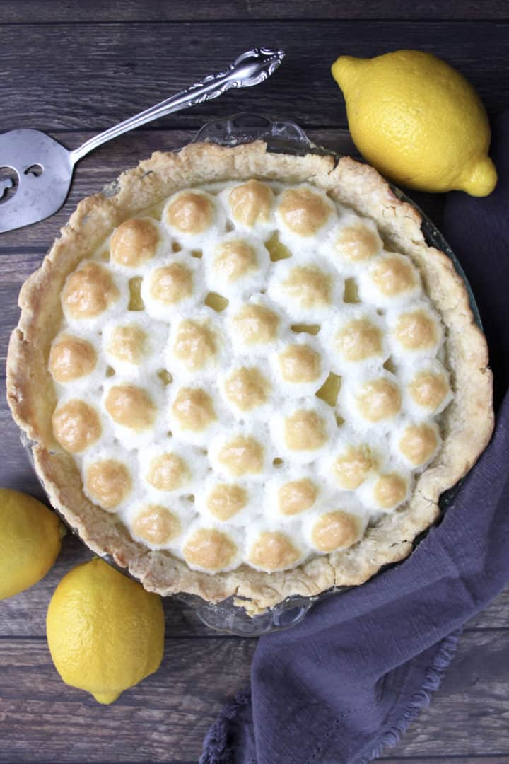 flat lay of gluten free lemon meringue pie with golden-tipped meringue