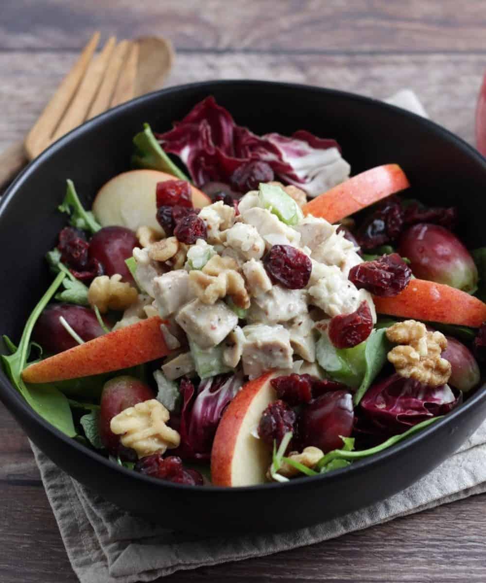 chicken waldorf salad in black bowl on linen napkin