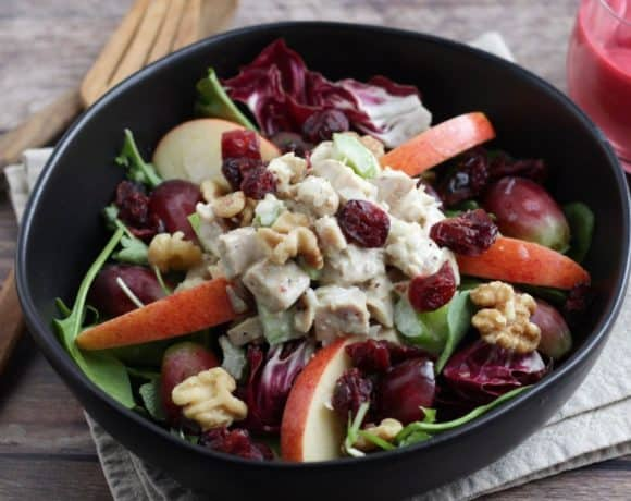 chicken waldorf salad in black bowl on linen napkin