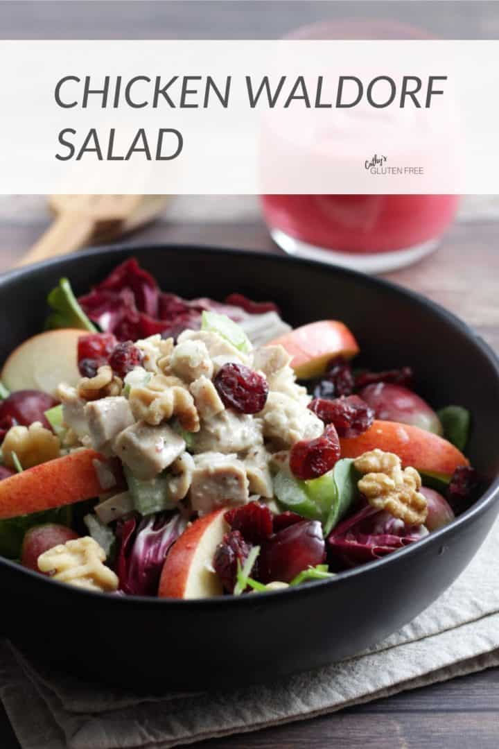 chicken waldorf salad in black bowl with raspberry vinaigrette on the side