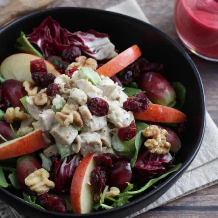 waldorf salad, with chicken salad, apples, grapes, dried cranberries, and walnuts on greens in black bowl