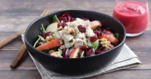 Chicken salad sits on a bed of greens with grapes, apples, walnuts, and dried cranberries. A bowl of raspberry vinaigrette sits to the side.