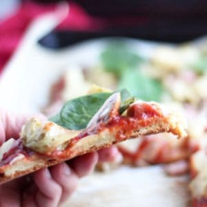 slice of thin-crust pizza held in hand