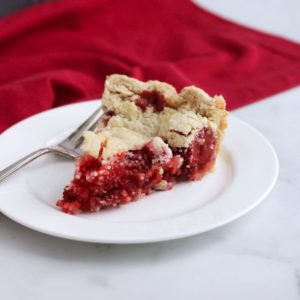 slice of pie with red strawberry rhubarb filling on white plate