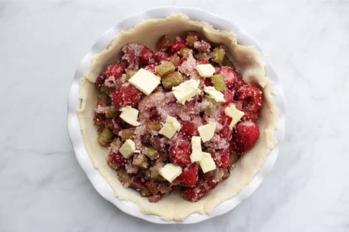 pats of butter scattered over strawberry rhubarb pie filling in bottom unbaked crust