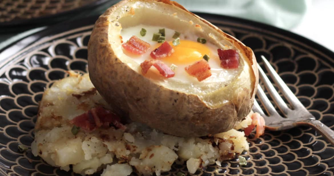 baked egg in hollowed out potato sprinkled with bacon bits and chives