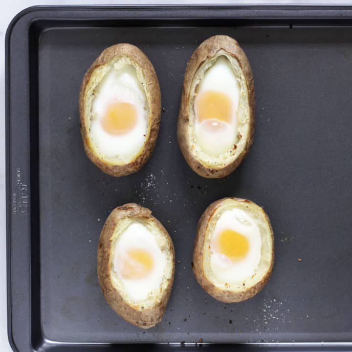 overhead view of 4 baked eggs in potato shells