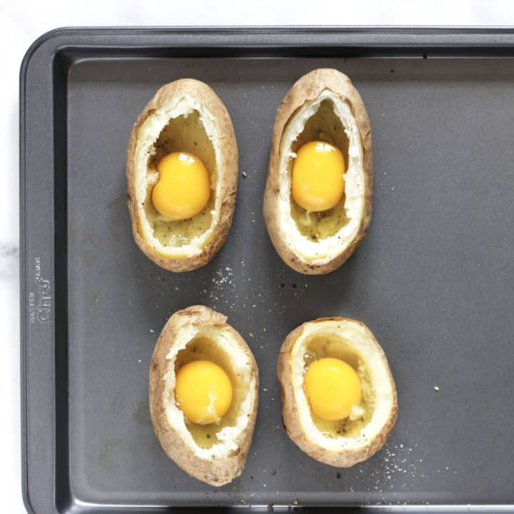 raw egg in each of four scooped out baked potato shells on tray