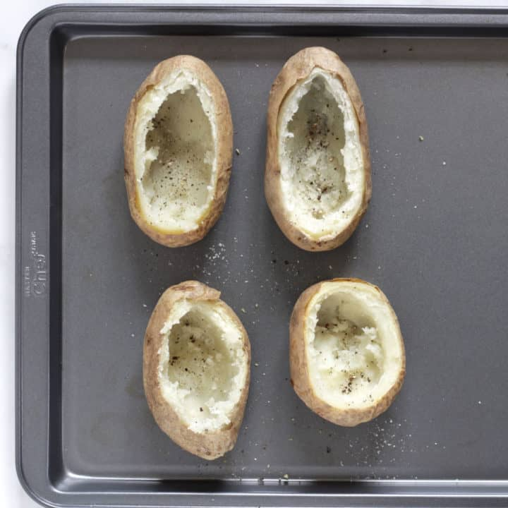 scooped out baked potato shells on baking tray