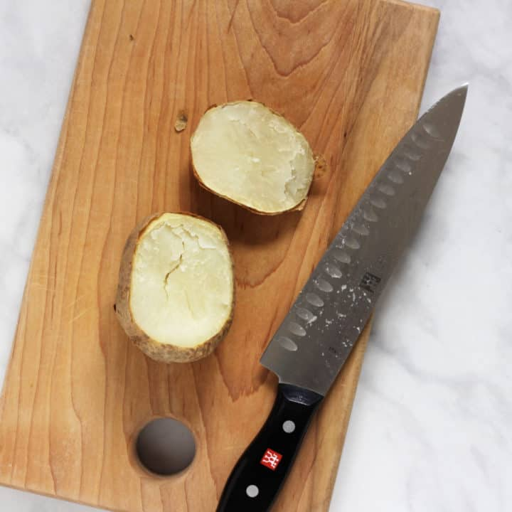 overhead view of baked potato with top sliced off on wooden cutting board with chef's knife