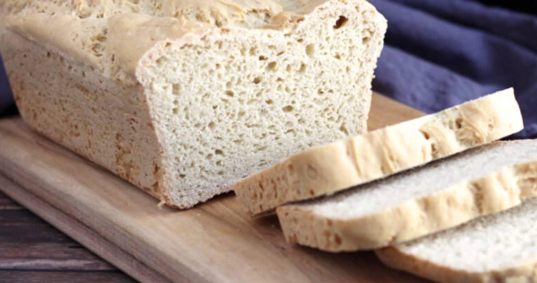 gluten free loaf of brioche bread partially sliced on wooden boarda