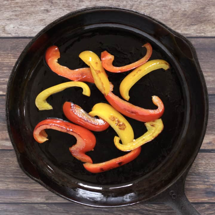 slightly charred strips of red and yellow peppers in cast iron frying pan