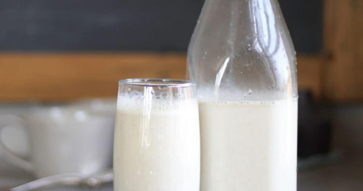 glass of white milk beside half-filled milk bottle