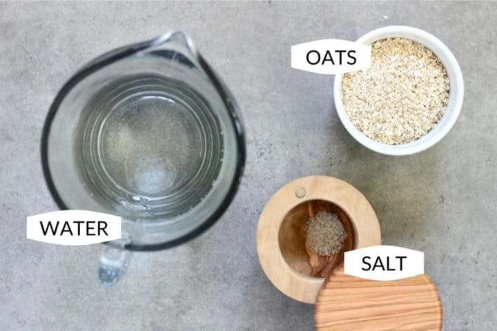flat lay of water in glass pitcher, white bowl of oats, and wooden cellar of salt