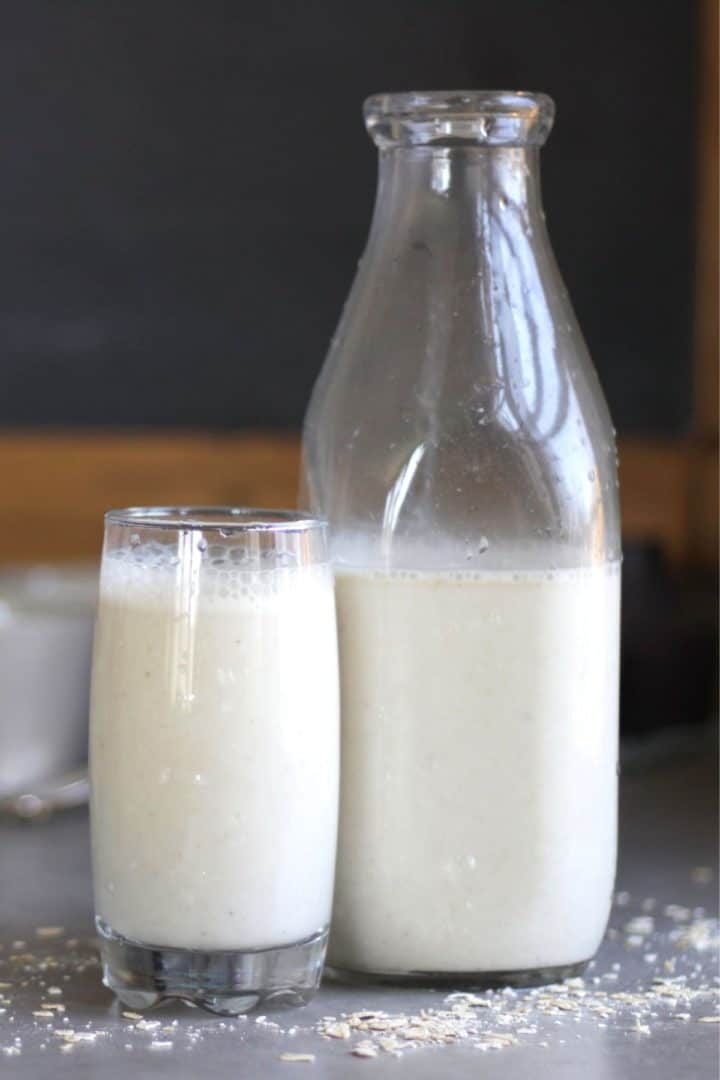 glass of milk standing beside a half-full milk bottle