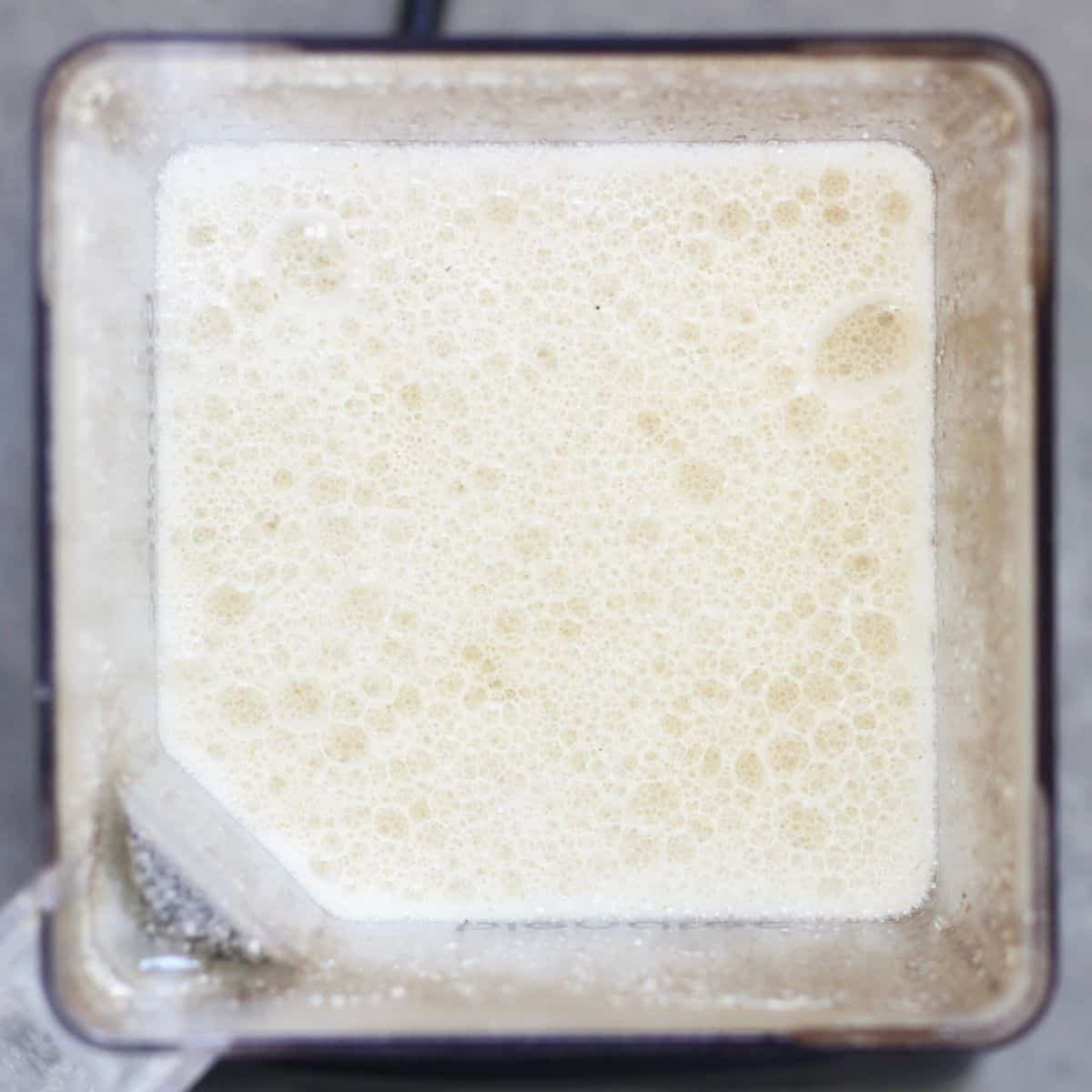 Frothy gluten free oat milk in blender, looking down from above