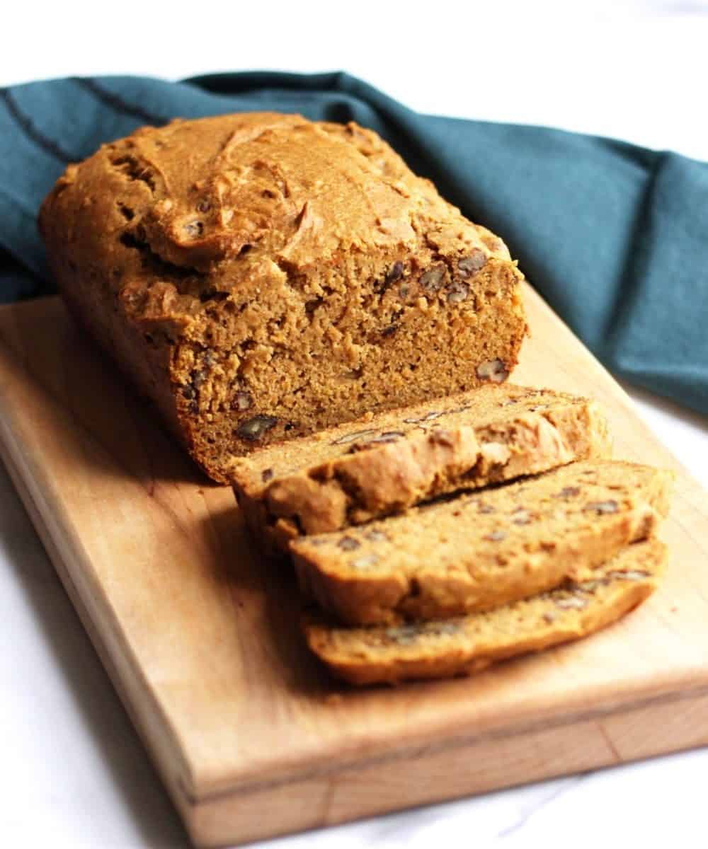 sweet potato bread partially sliced on wooden board with teal napkin in background
