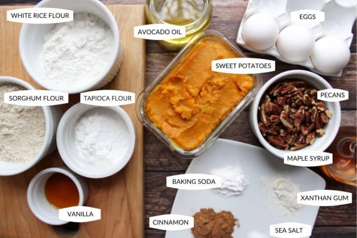 Gluten free flours, cooked sweet potato, eggs, pecans, and other ingredients laid out to make sweet potato bread
