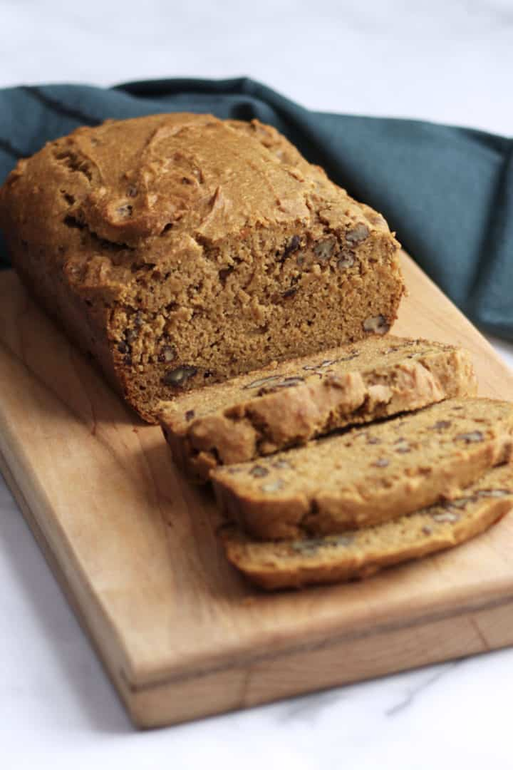 partially-sliced gluten free sweet potato loaf on wooden board