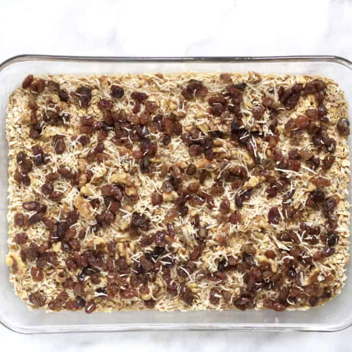 raisins, coconut, and nuts spread over oat layer in glass pan