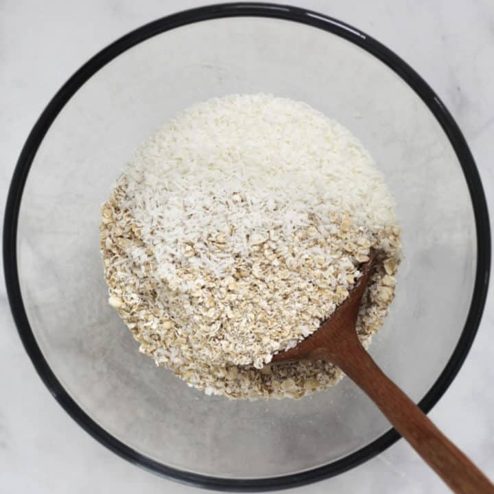 dry oats and coconut stirred in a glass bowl with a wooden spoon