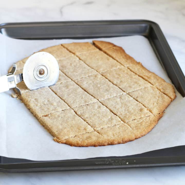 dough with toasted brown edges being cut into rectangles with a pizza cutter