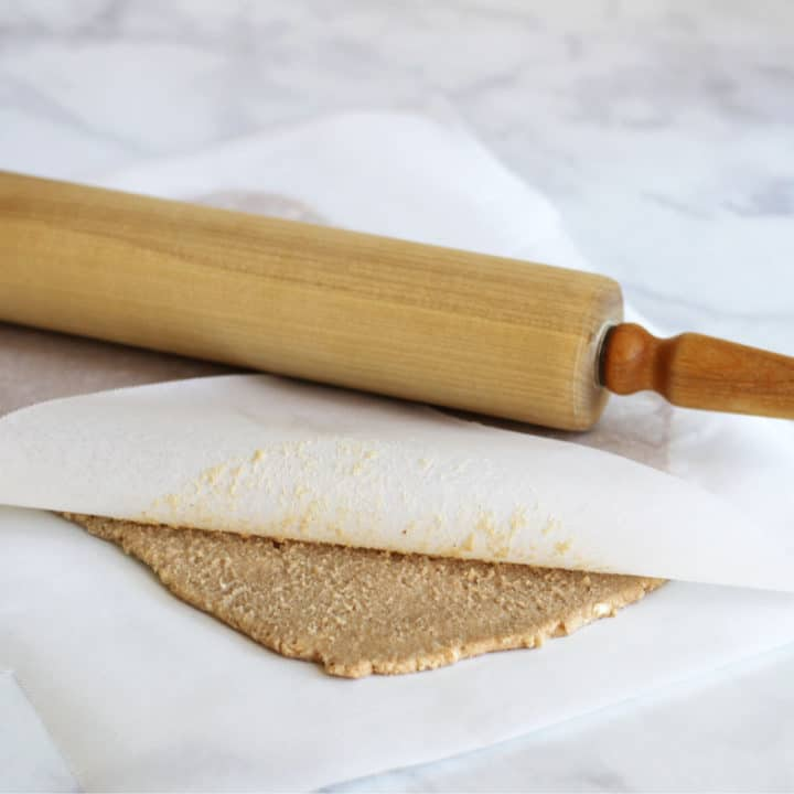 rolled dough between two sheets of parchment paper with rolling pin on top