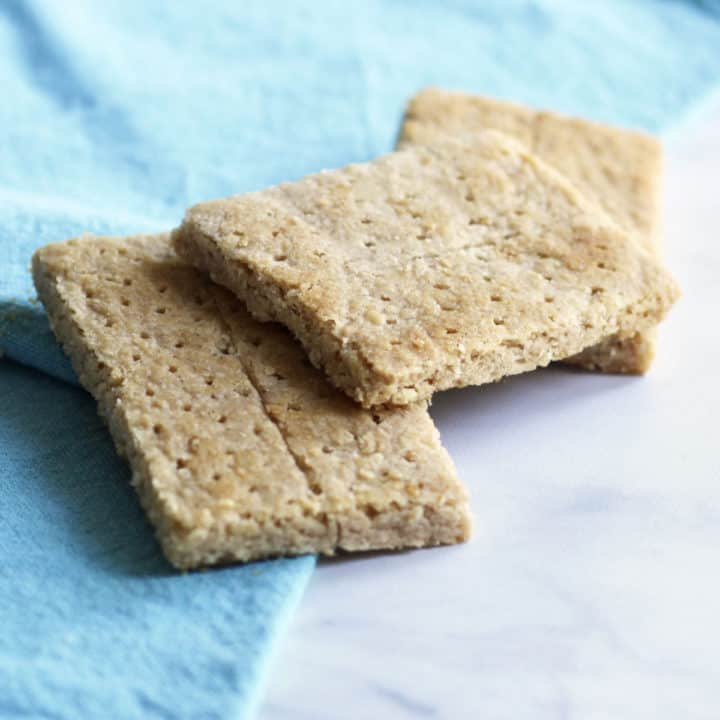 three gluten free graham crackers on a turquoise napkin, viewed from an angle