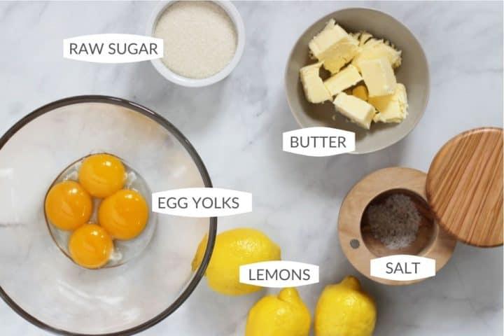 5 ingredients for lemon curd: lemons, egg yolks, butter, salt, and raw sugar