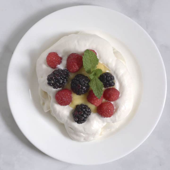 fresh berries and mint leaves on a cloud of whipped cream, seen from above