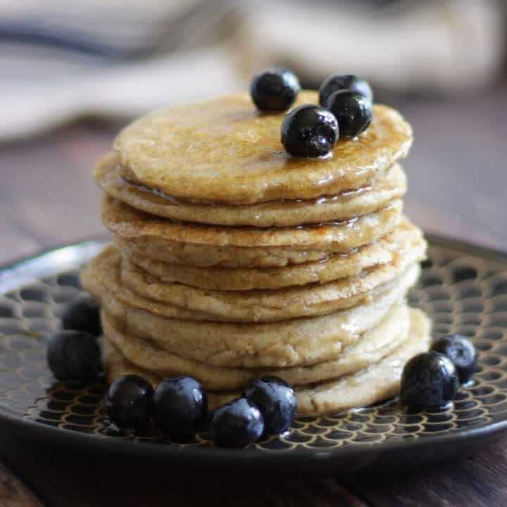 stack of pancakes with blueberries and syrup on top
