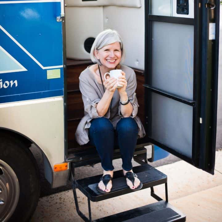 Cathy sitting on steps of motorhome doorway holding a cup of coffee