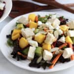 cubes of chicken, mango, and avocado sit with slivers of carrot and beet on lettuce and kale salad