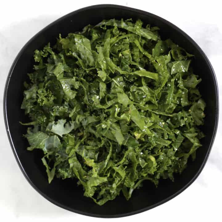 shredded kale glistening with salad dressing sitting in a black bowl