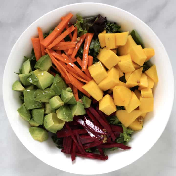 cubes of mango and avocado arranged in white bowl with slivers of beet and carrot, all glistening with salad dressing