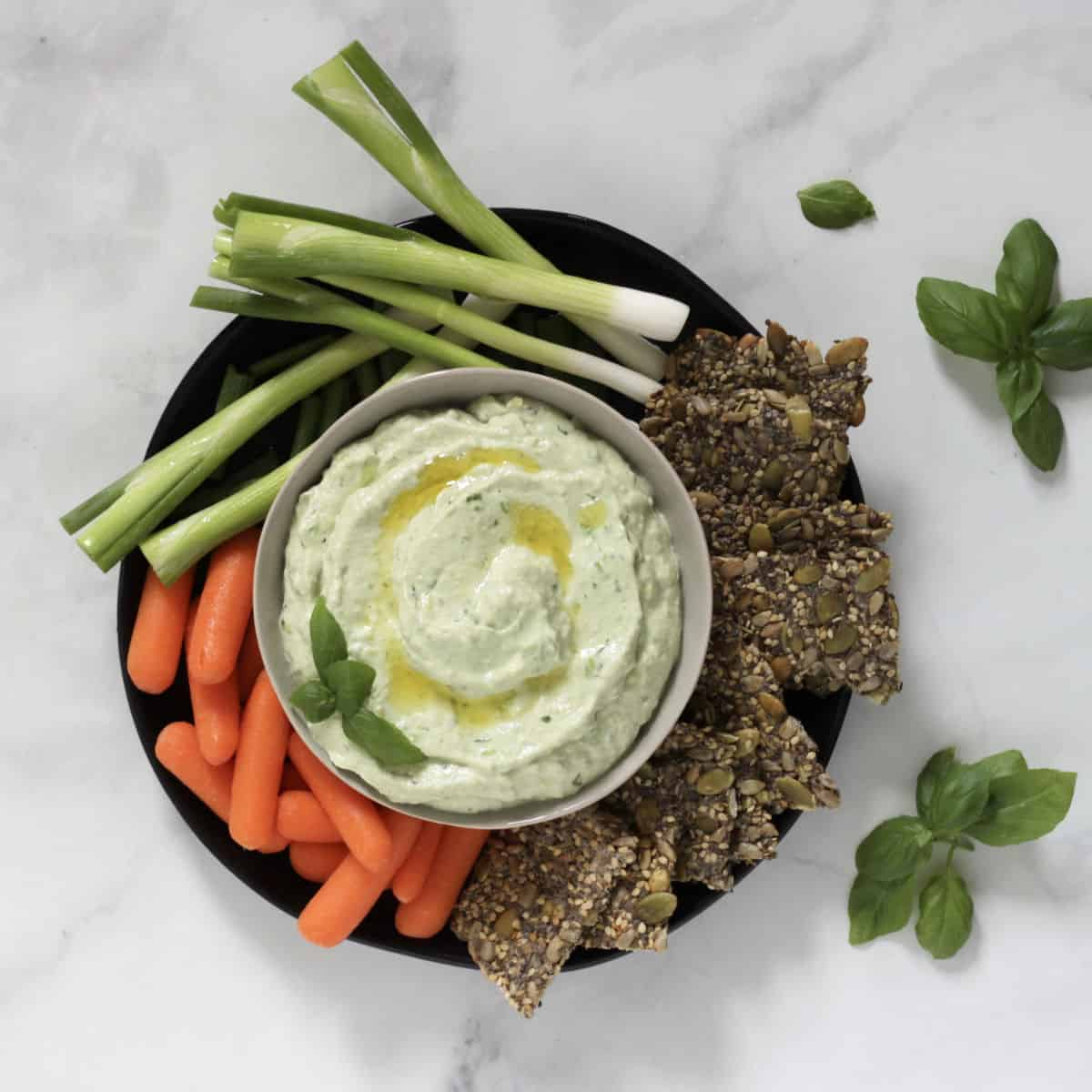 looking down on a bowl of greenish, creamy dip surrounded by carrots, green onions, and crackers