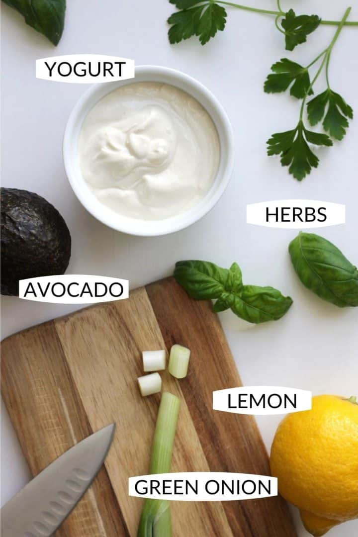 top down view of each of the individual ingredients for vegan avocado dip on marble with wooden cutting board