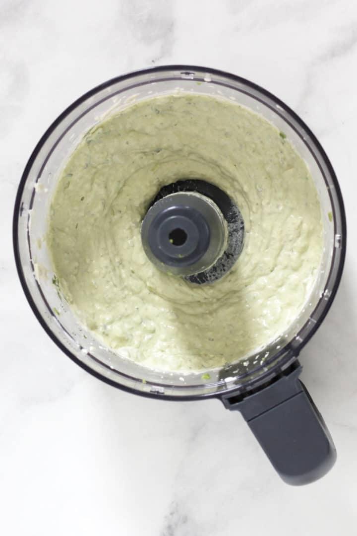 greenish, creamy veggie dip in bowl of food processor