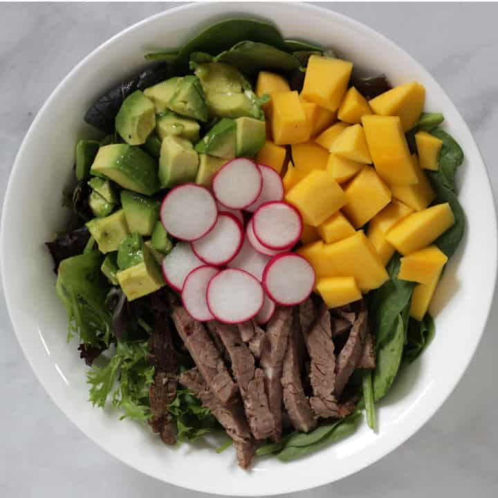 looking down of a white bowl of mango and avocado chunks, slices of roast beef and radish, lettuce