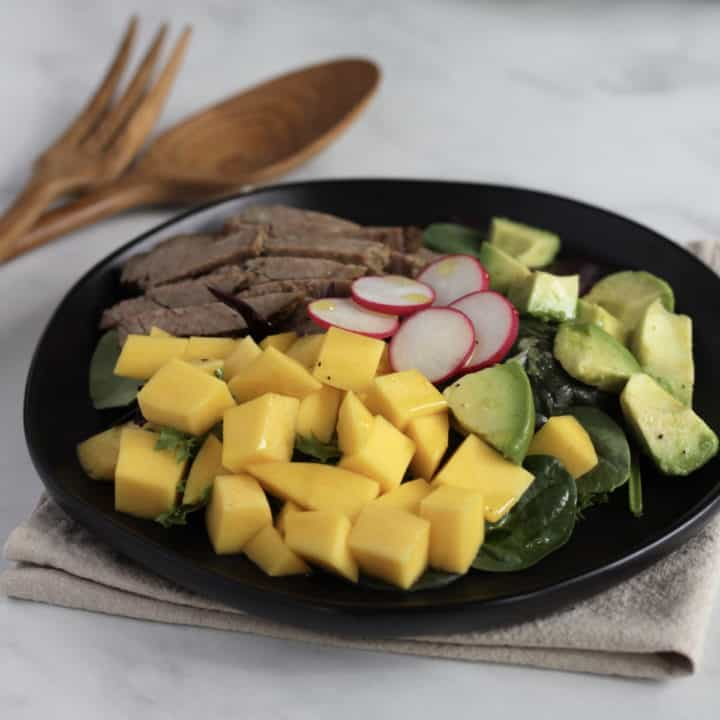 chunks of mango and avocado with roast beef and radishes viewed from an angle