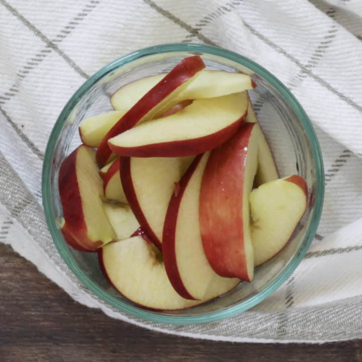 apple slices in glass bowl sitting on white, checked towel
