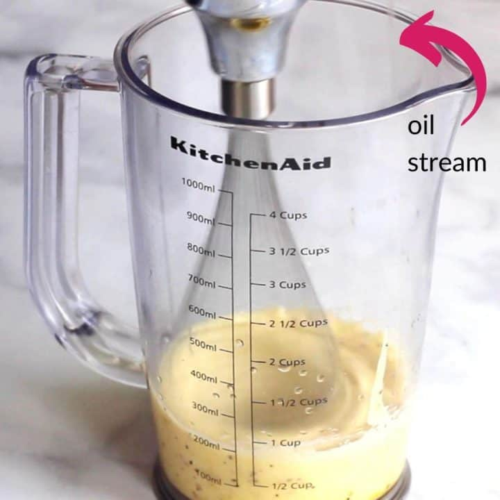 mayonnaise thickening up with pink arrow pointing out small stream of oil
