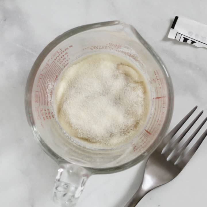 white powdered gelatine sprinkled over liquid in pyrex measuring cup with fork to side