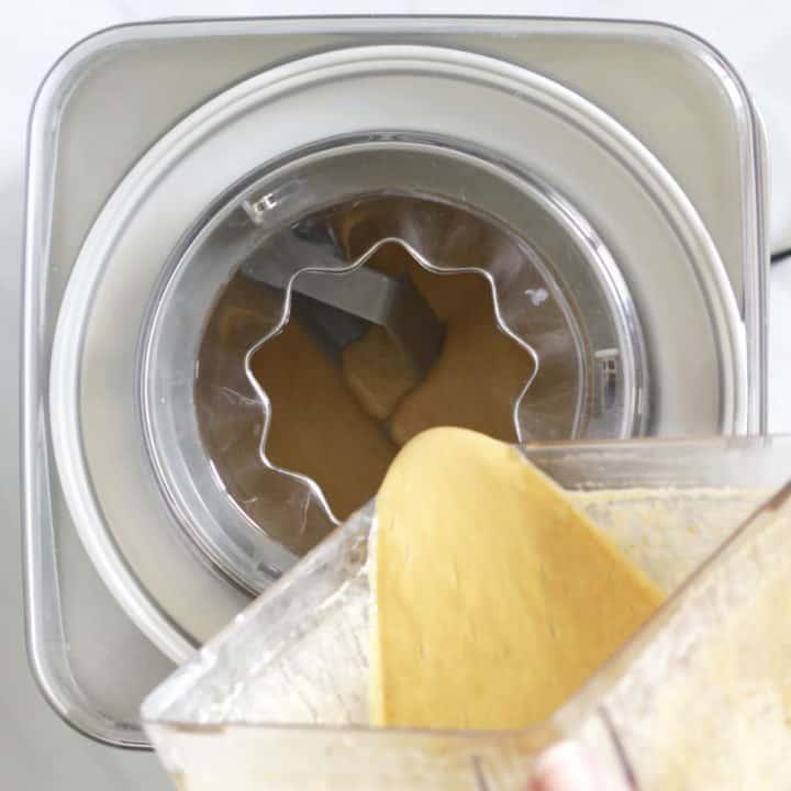 golden liquid being poured from blender jar into ice cream maker