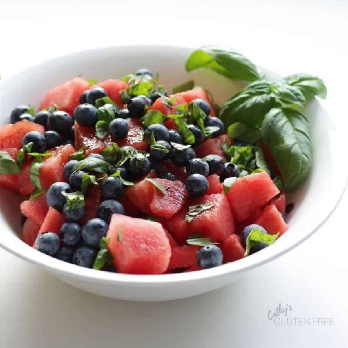 watermelon chunks, blueberries, and chopped basil in white bowl