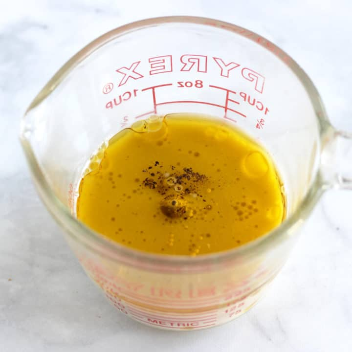 golden liquid with salt and pepper sprinkled on top in pyrex measuring cup